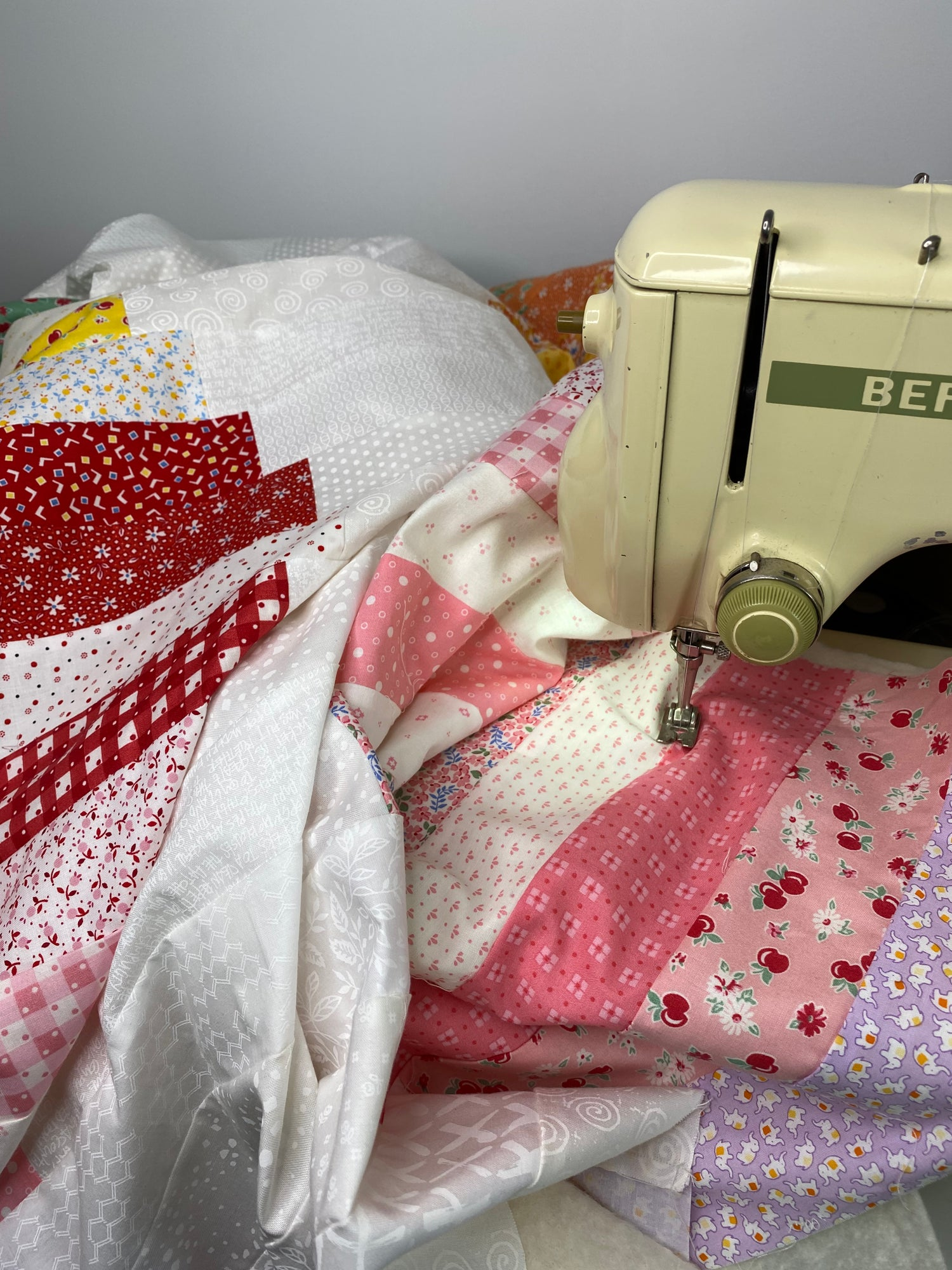 An antique Bernina Sewing Machine in the process of quilting a modern patchwork quilt top.