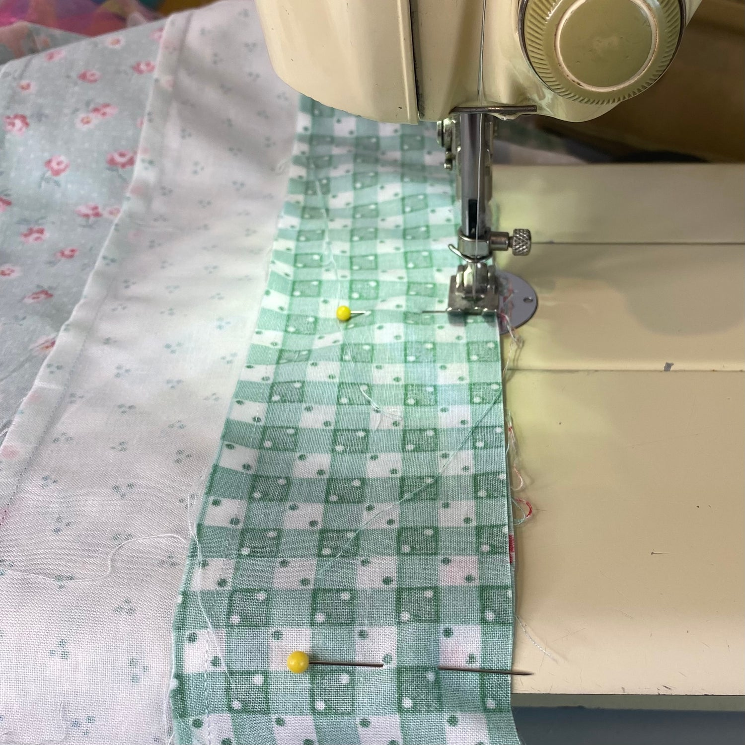 """Tips for maintaining a quarter inch seam allowance even when you don't have a 1/4"""" quilting foot for your sewing machine. Picture shows an antique sewing machine sewing a 1/4"""" seam allowance on a modern quilt."""