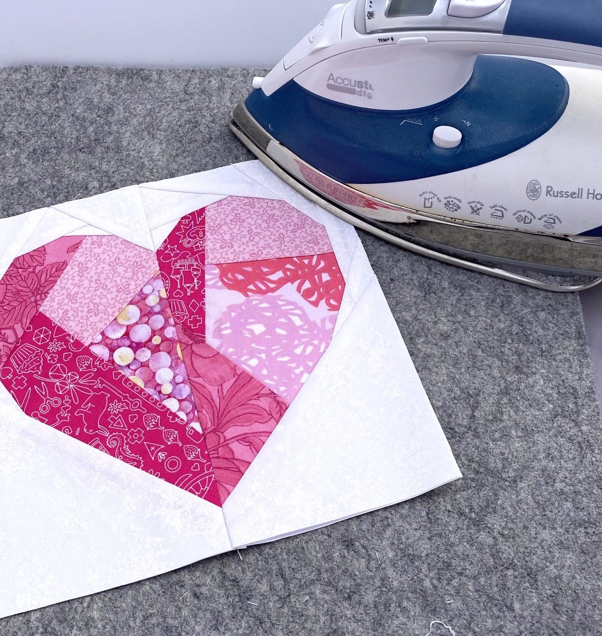 Pressing a paper pieced heart quilt block. Paper pieced geometric heart quilt block being pressed on a wool pressing mat by a Russell Hobbs Iron.